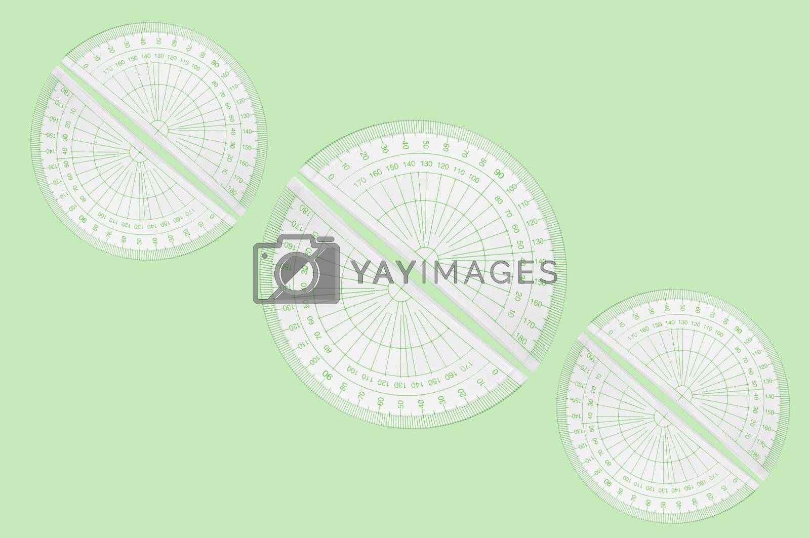 Several plastic protractors arranged in formation over pale green background.