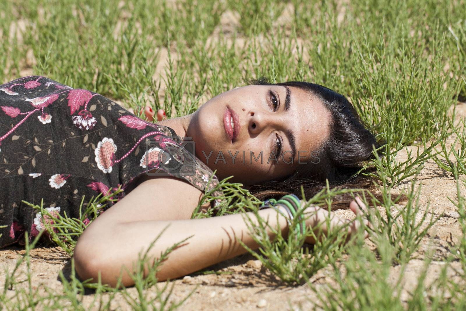 Beautiful girl with floral dress on the ground in a sunny day.