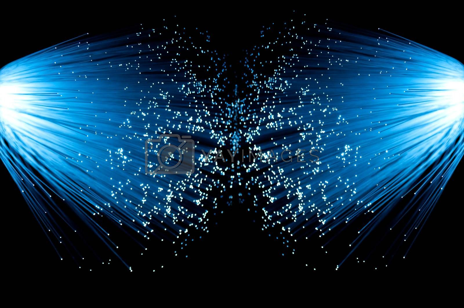 Two illuminated groups of blue fibre optic strands emanating from the left and right of the image. Black background.