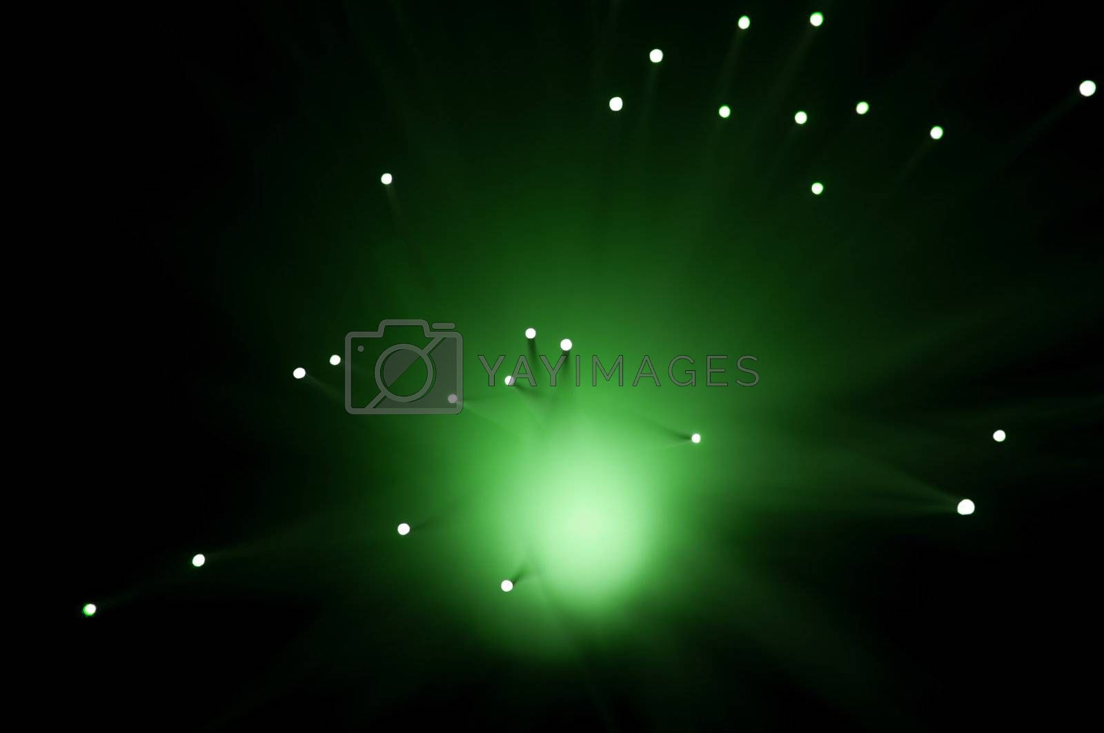 Abstract style capturing the ends of green illuminated fibre optic strands against black.