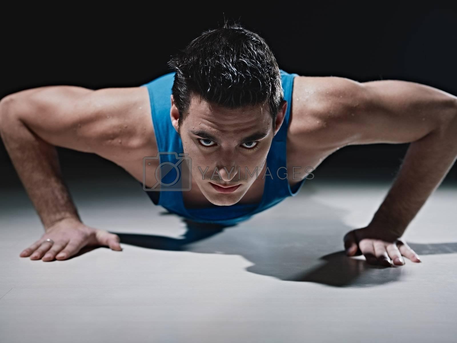 Man doing push-ups on black background by diego_cervo