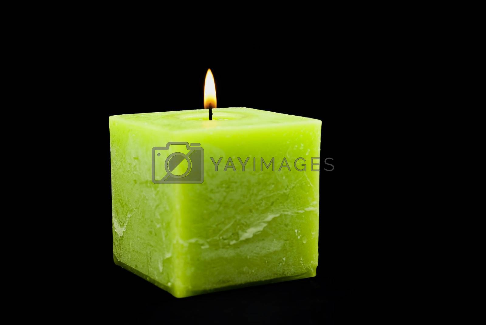 a green candle on a black background.