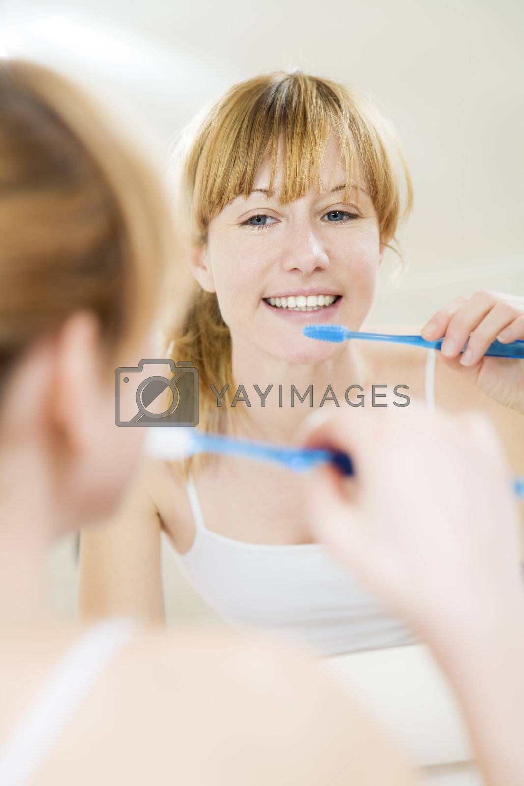 Young woman looking into a mirror brushing her teeth