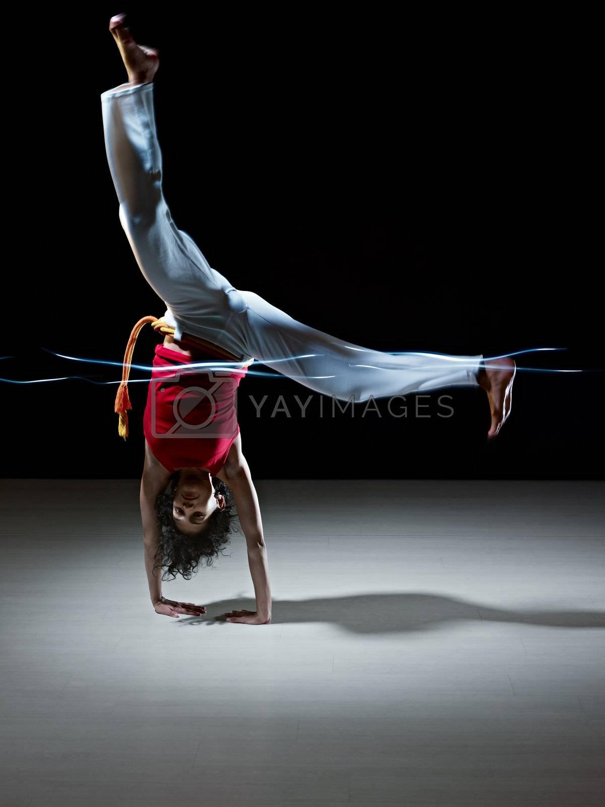 hispanic woman doing capoeira martial art by diego_cervo