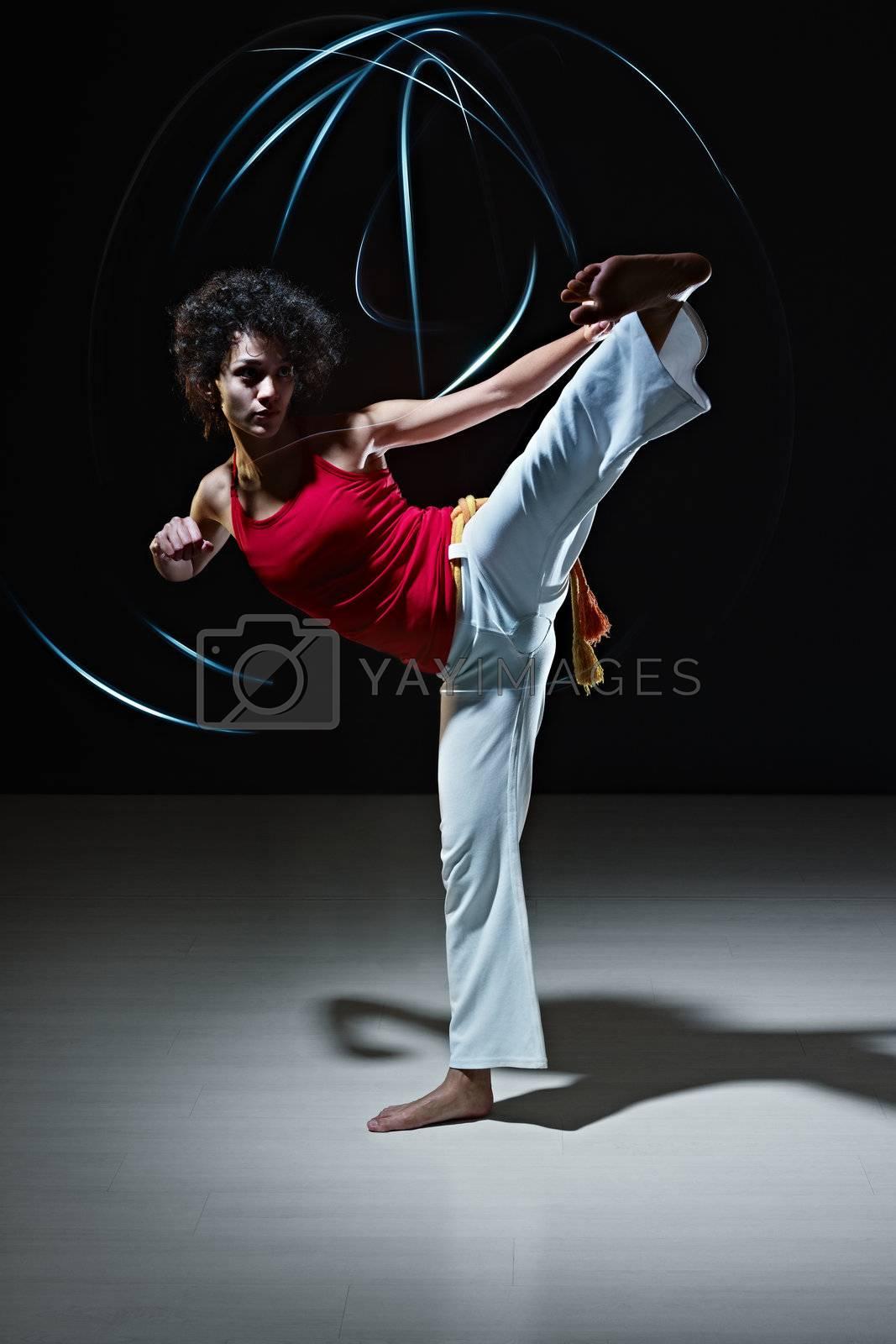 hispanic woman playing capoeira martial art by diego_cervo