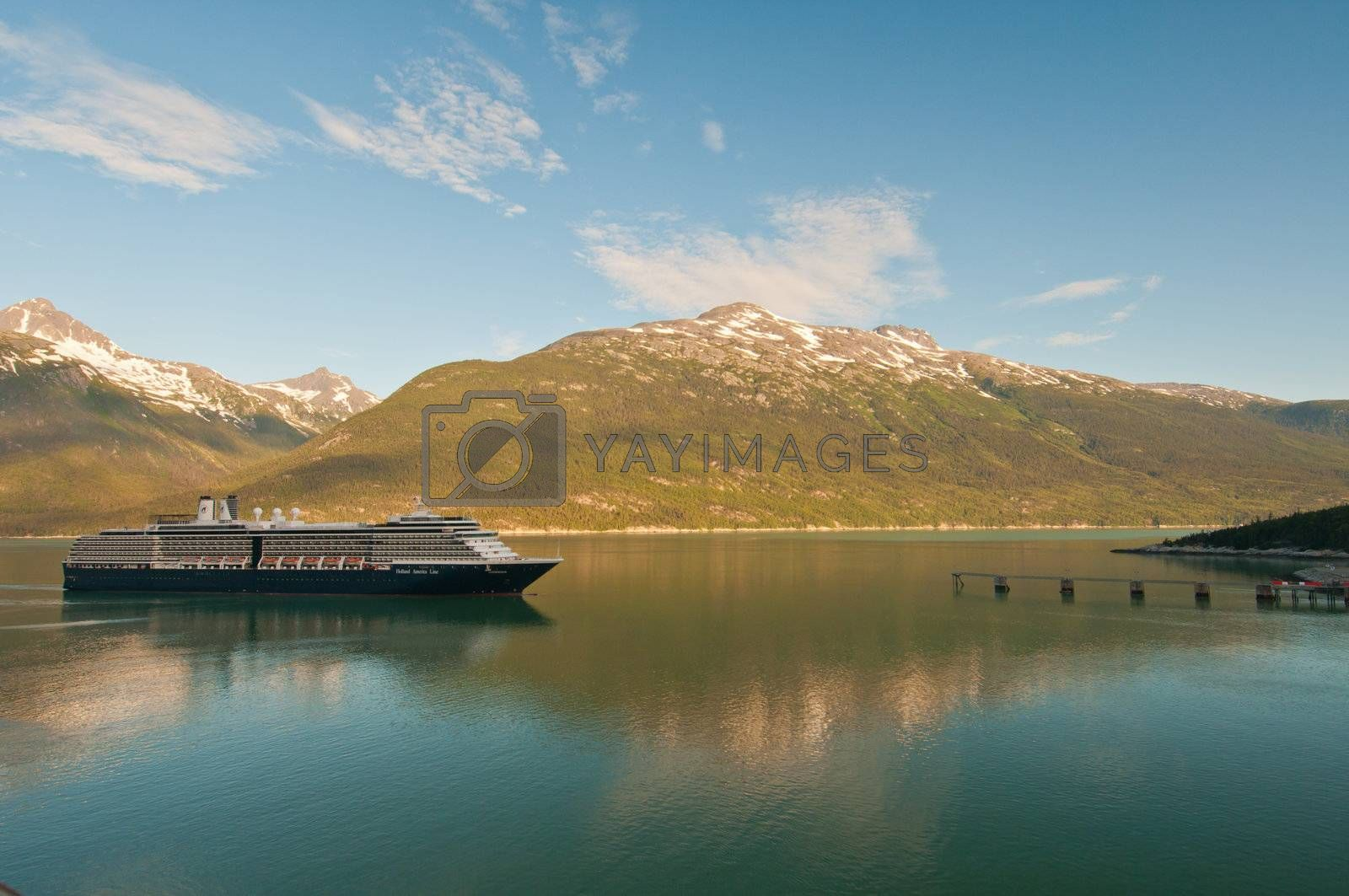 Cruise ship reaching and sailing into detination port with beautiful mountains.