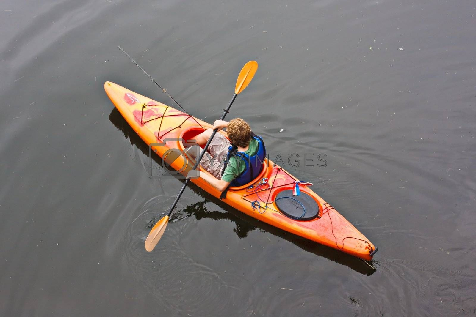A teenage boy paddling a kayak on a lake. There is a fishing pole in the kayak with him.