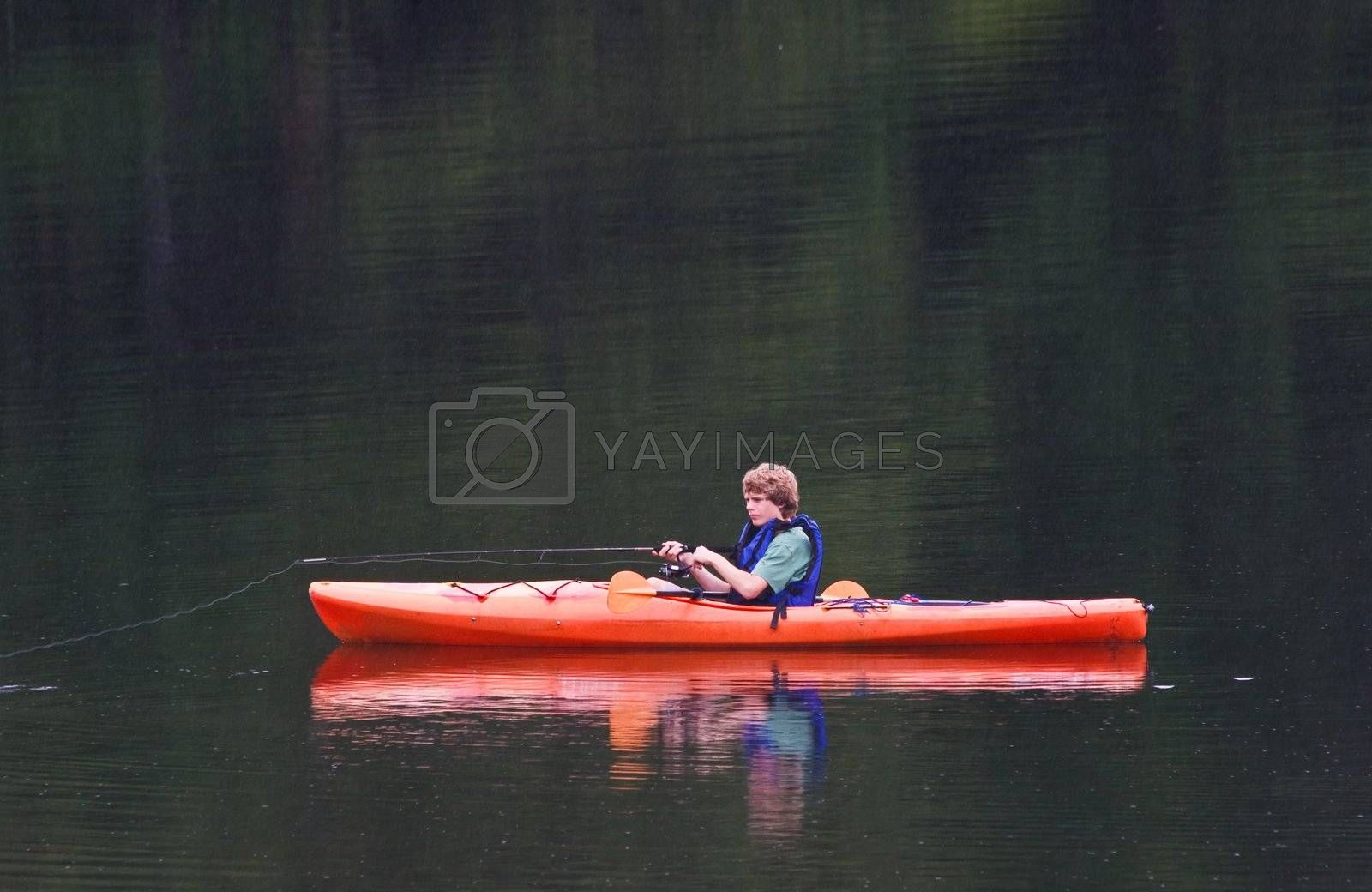 A young teenage boy fishing from a kayak in the evening. It is raining and streaks of rain can be seen against the lake background.