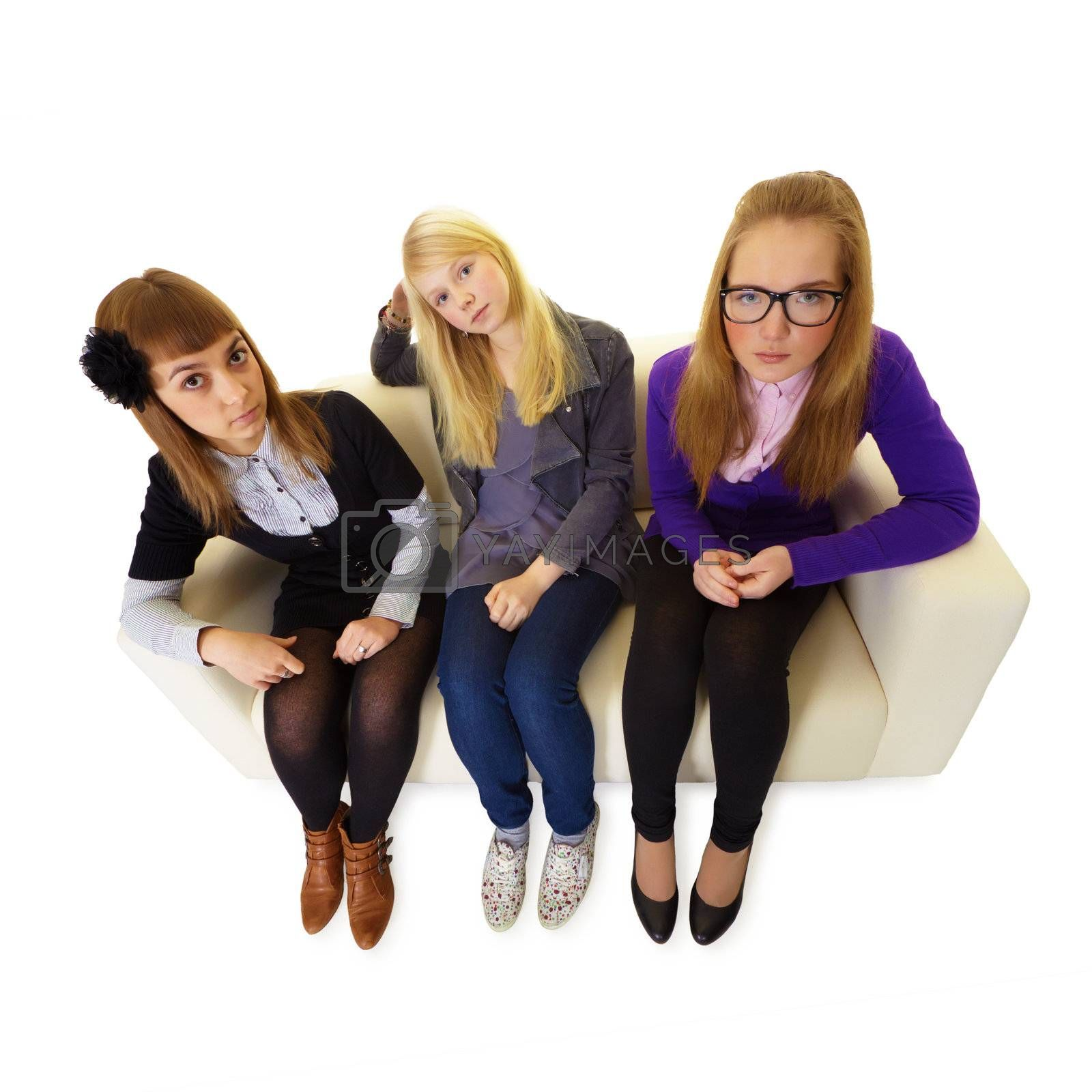 Three girlfriends are sitting on a sofa on white isolated background