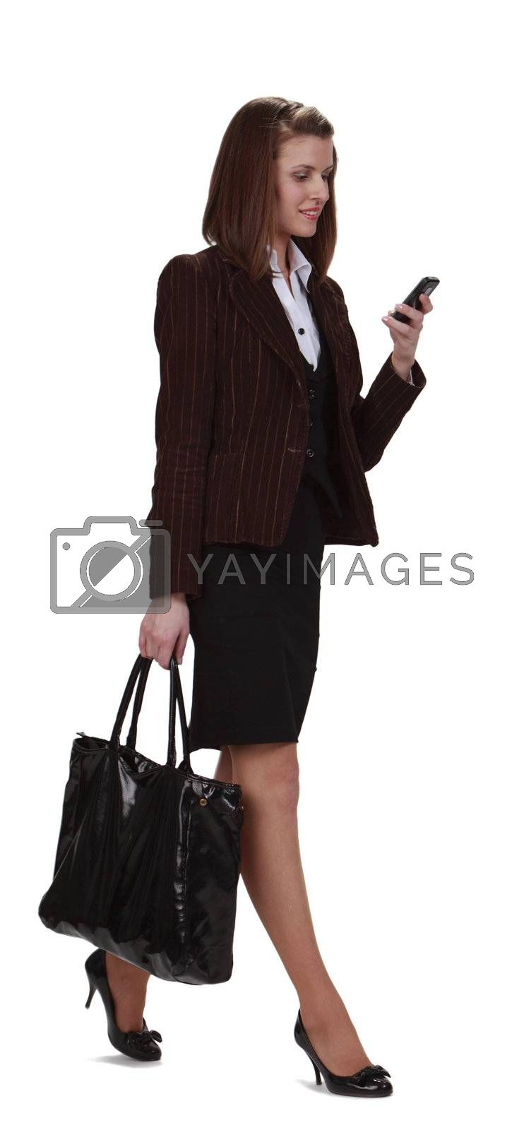 Young businesswoman checking her mobile phone while is walking,isolated against a white background.