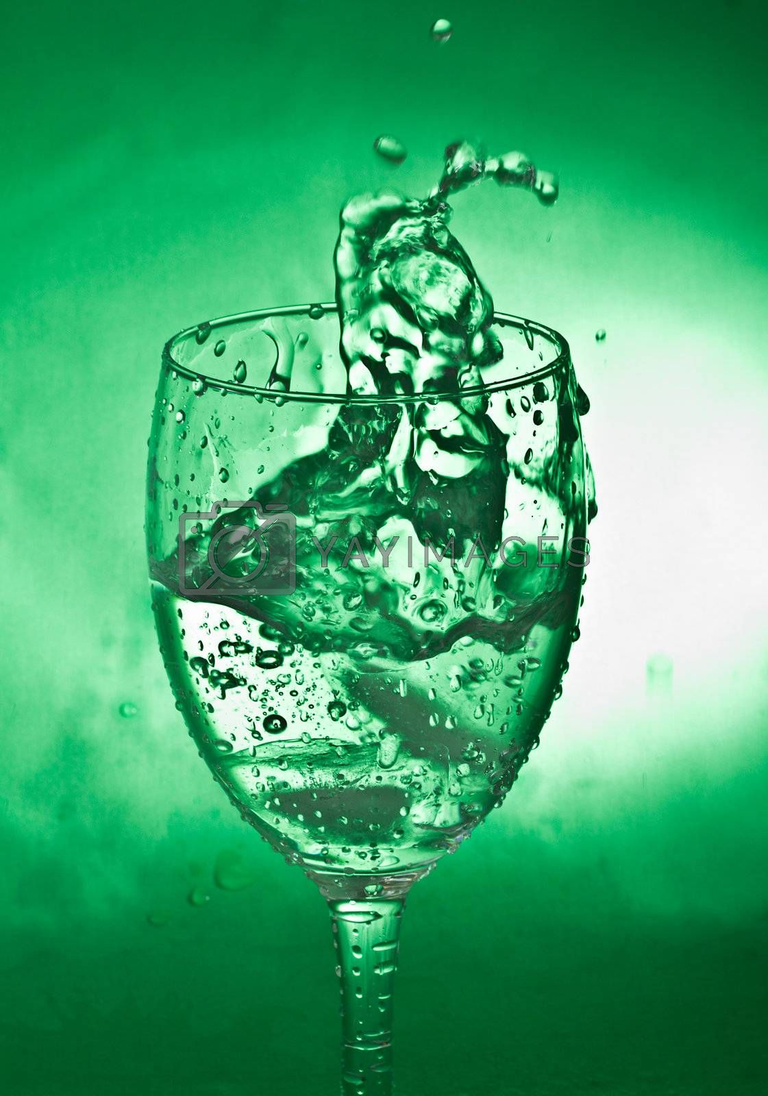 close-up glass with water splash on green background