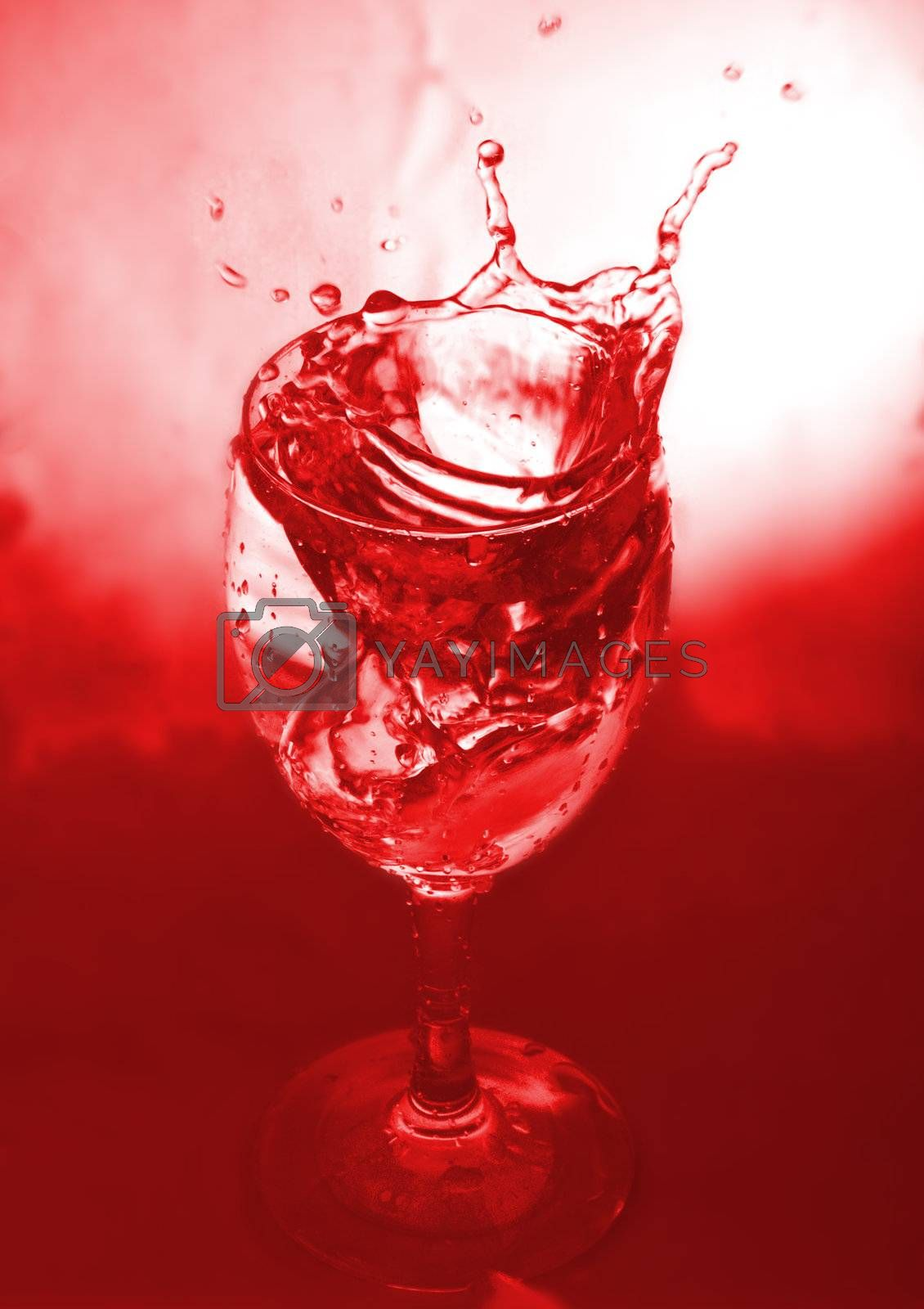 close-up glass with water splash on red background
