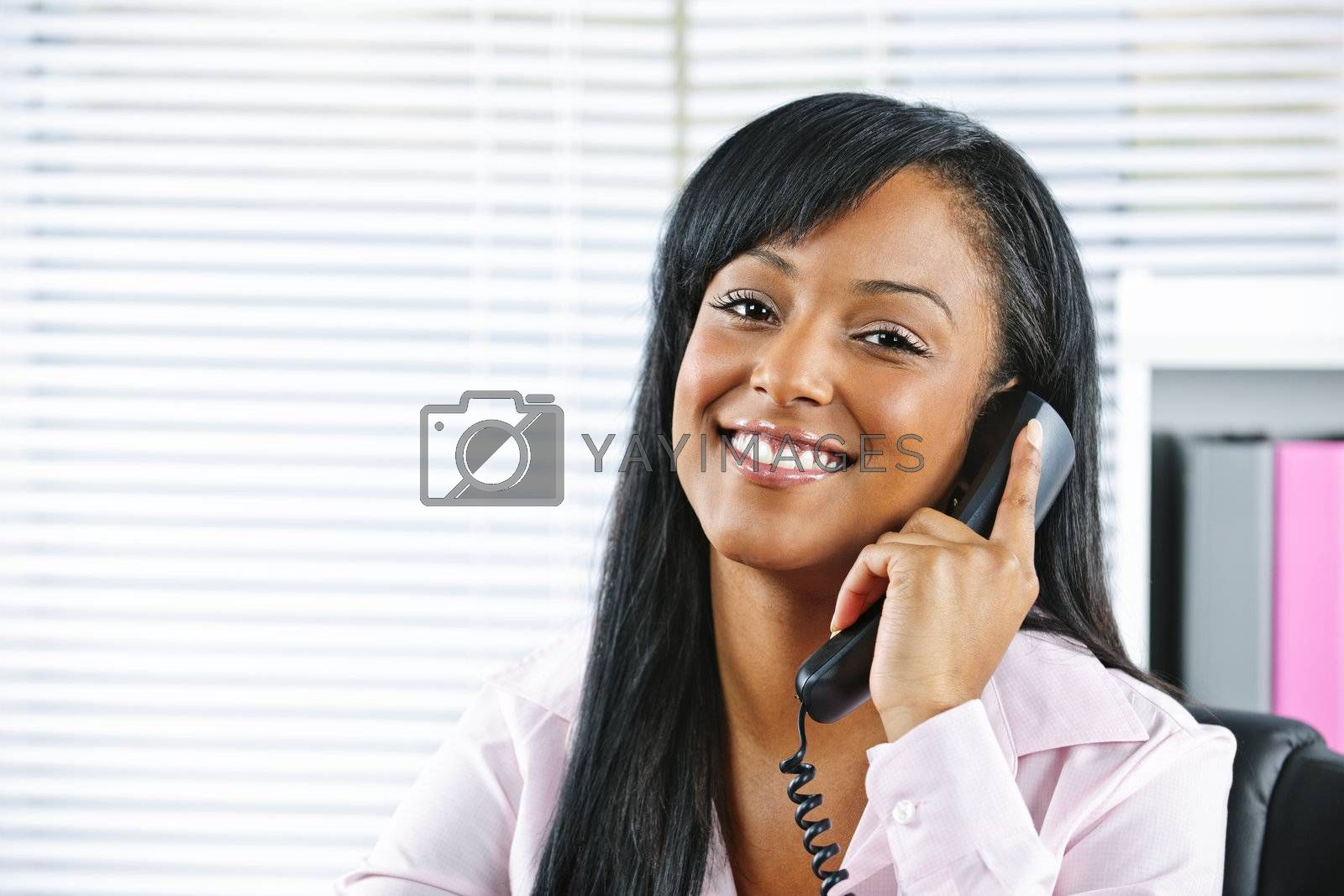 Young black businesswoman talking on phone by elenathewise