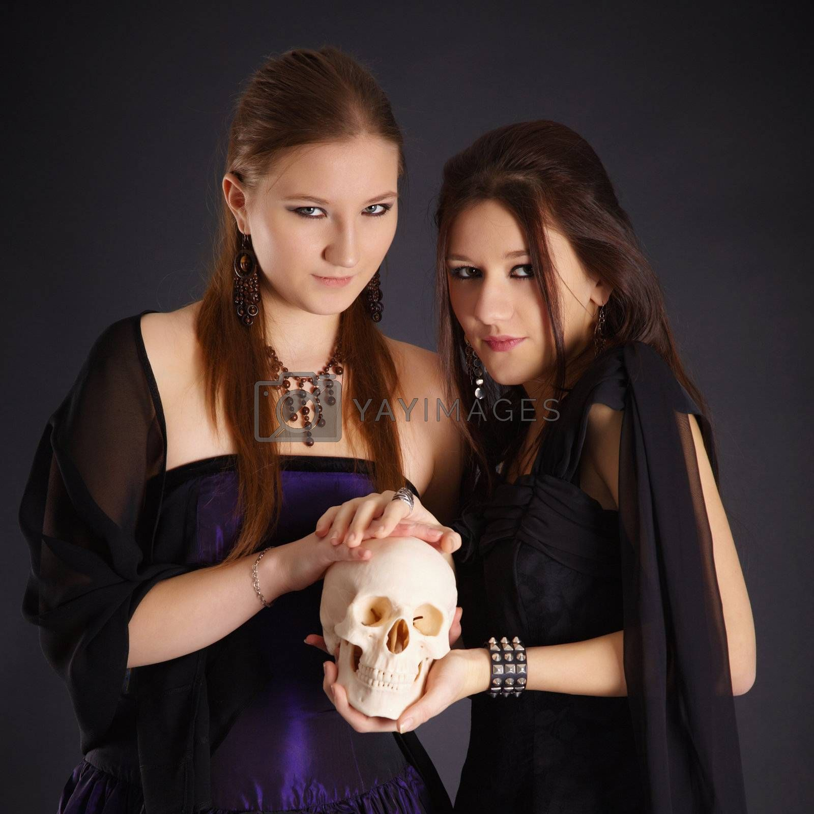 Two young girls in the dark with a human skull