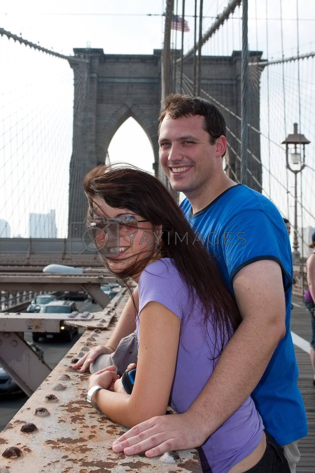 A smiling couple of tourists visit Brooklyn New York by the world famous Brooklyn Bridge.