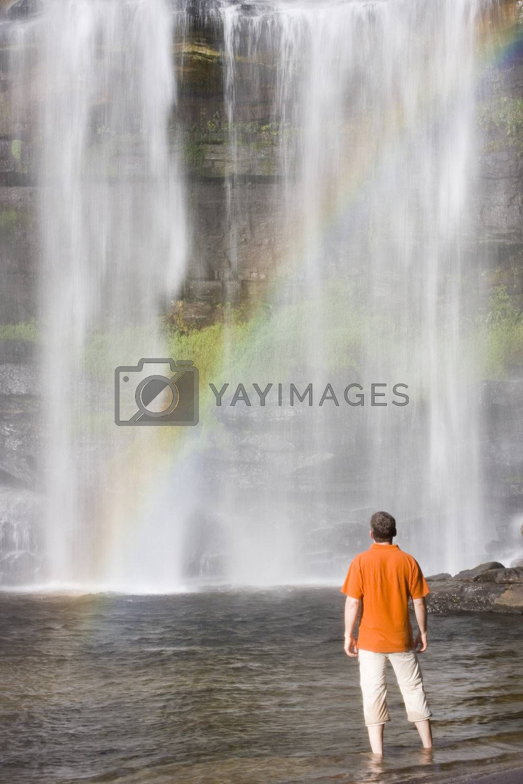 Man standing in front of a tropical waterfall with rainbow.