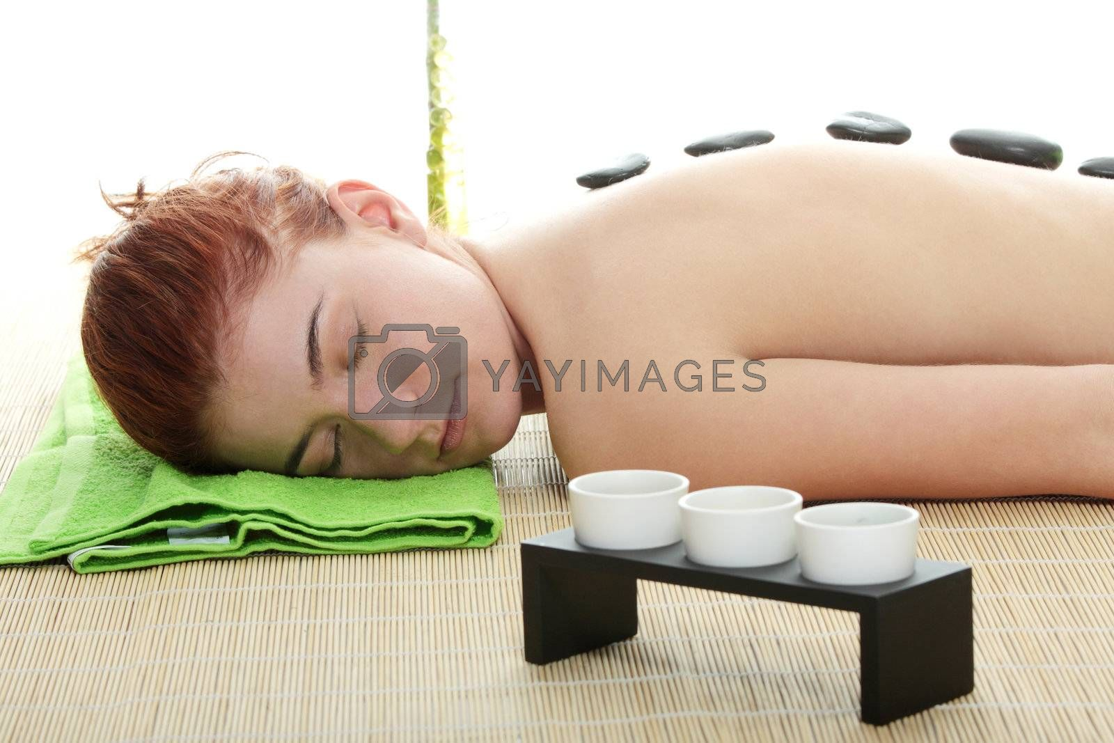 Young woman in spa with rocks on her back, isolated