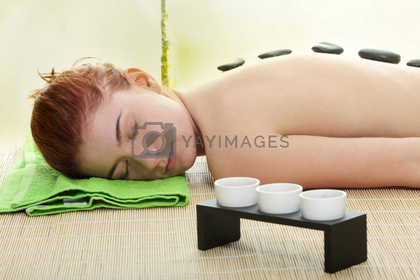 Young woman in spa with rocks on her back