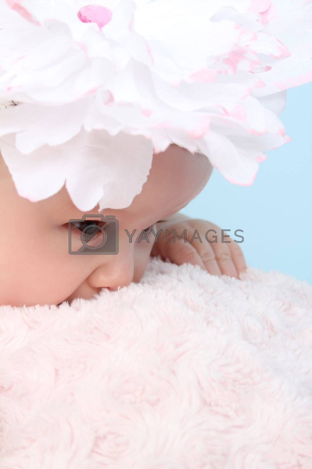 Cute baby girl with a flower hat on a fluffy pink blanket