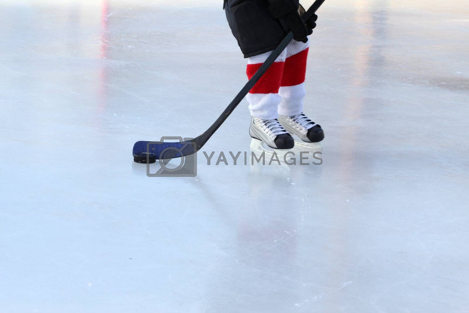 Young hockey player practising on a frozen pond