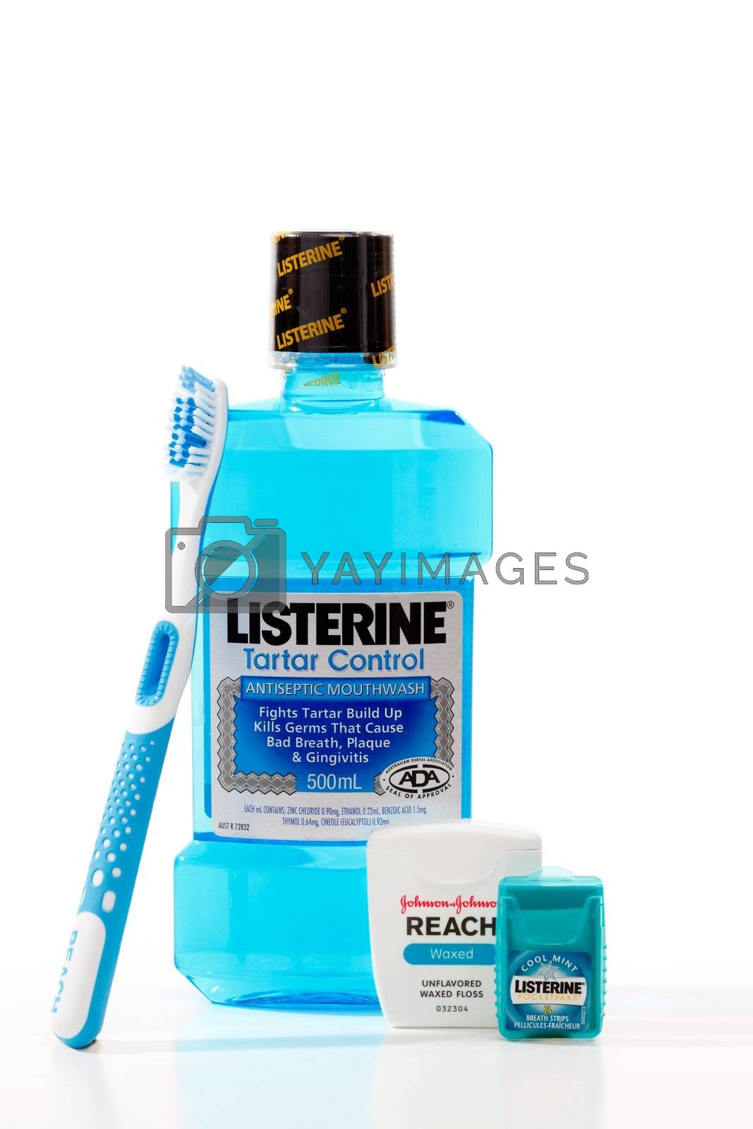 Four dental hygiene products made by Johnson and Johnson.   Products from left to right are, Reach toothbrush, Listerine Tartar Control antiseptic mouthwash, Reach waxed dental floss, and Listerine Pocketpaks Cool Mint breath strips.  Photographed in studio on a white background.  Editorial use only