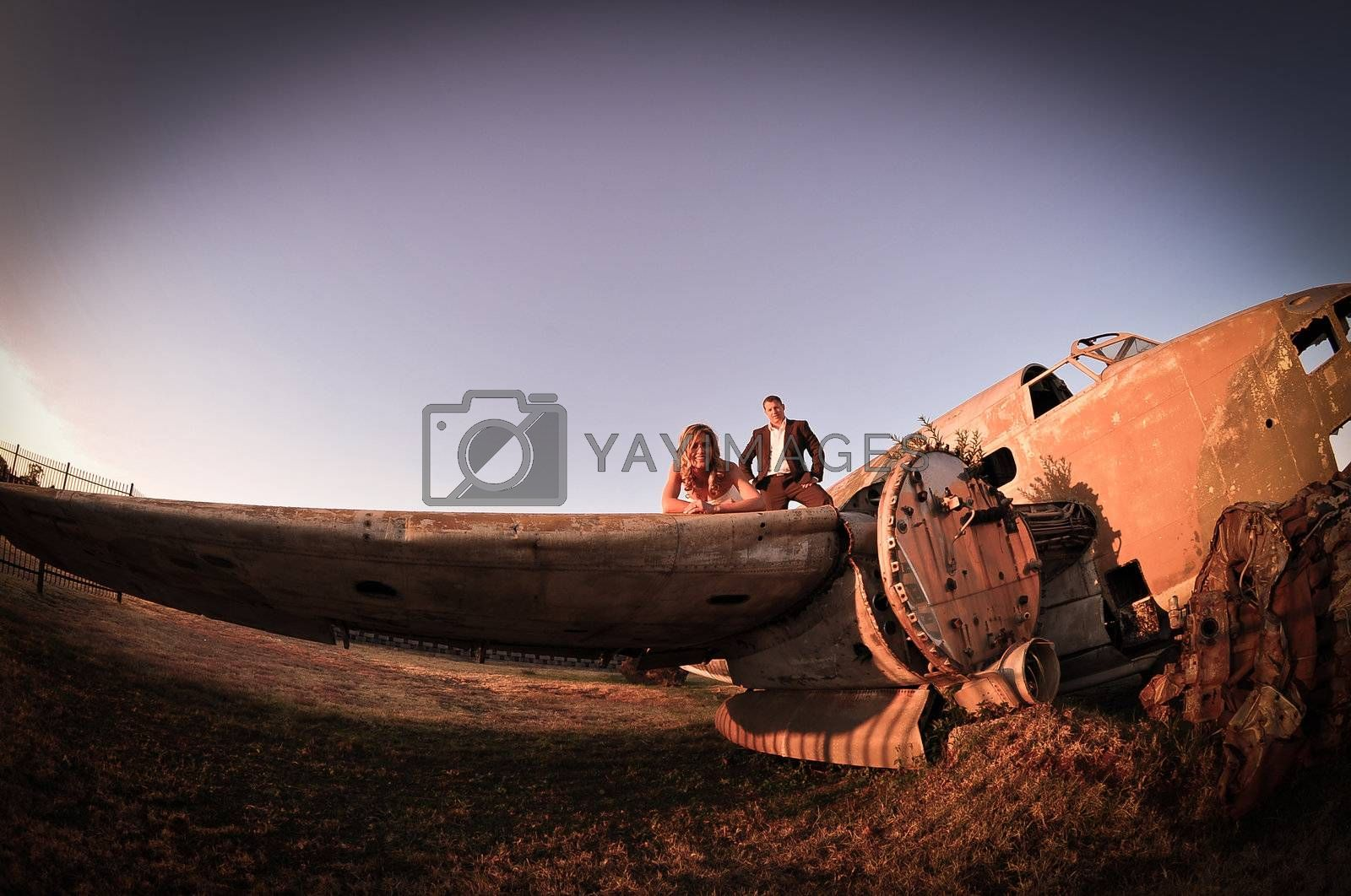 young wedding couple standing at crashed old Dakota war plane by Ansunette