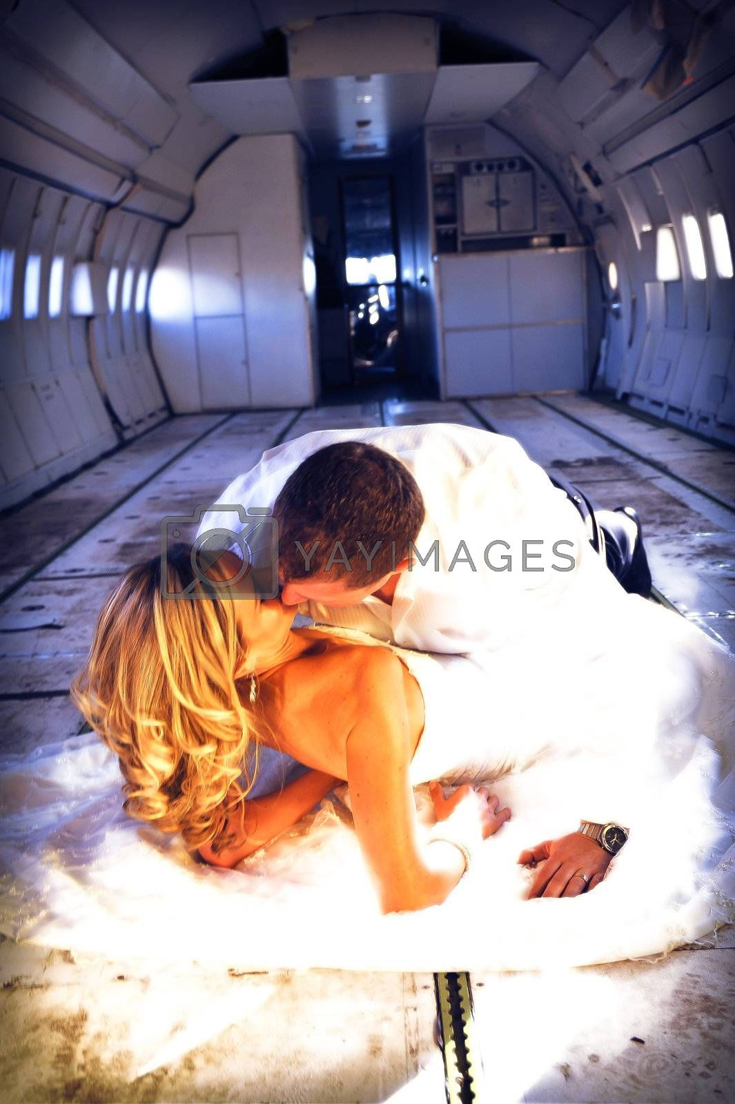 sexy young  adult wedding couple laying in the fuselage of airplane