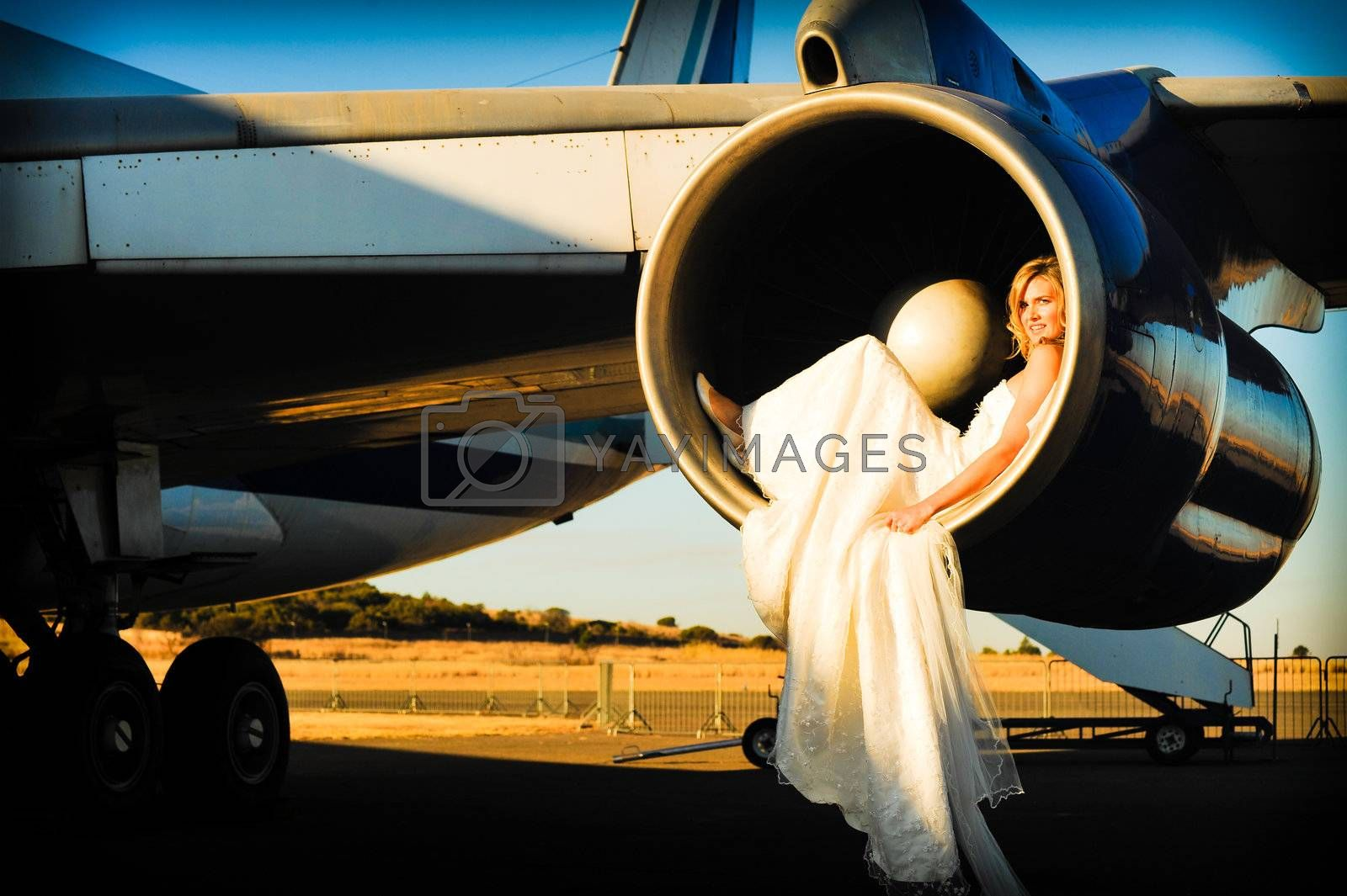 sexy young adult wedding model laying inside the engine intake of  passenger aircraft
