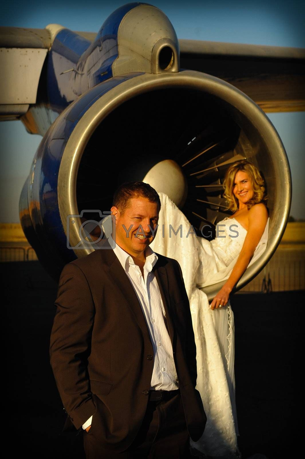 sexy young adult wedding couple laying inside the engine intake of Boeing passenger aircraft with groom infront