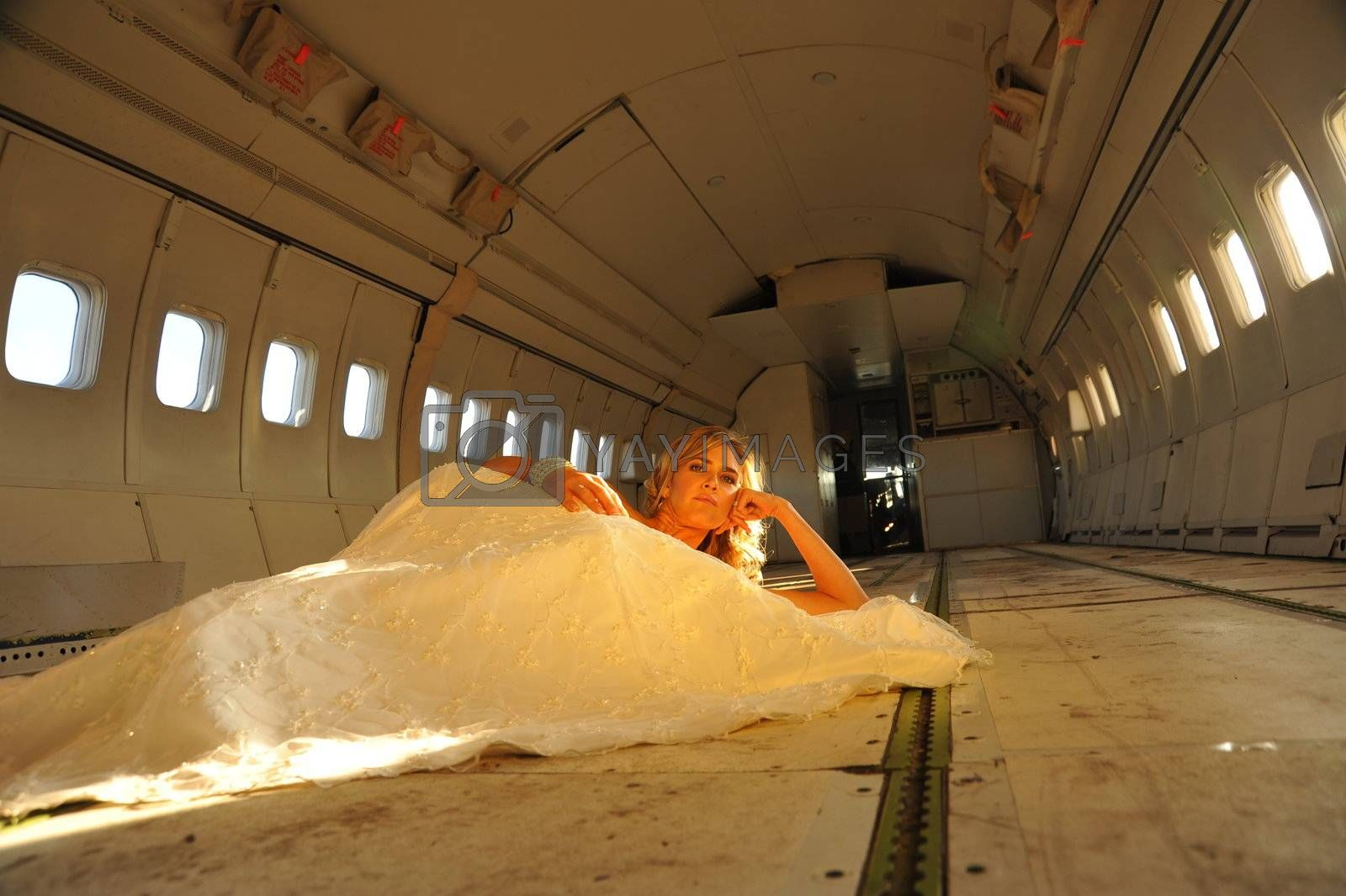 sexy young  adult wedding model laying in the fuselage of airplane