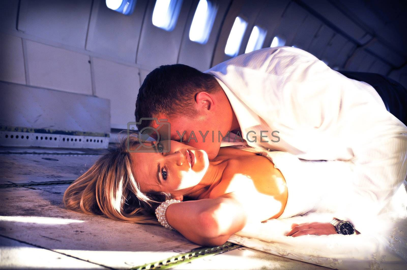 sexy young  adult wedding couple laying in the fuselage of airplane and kissing