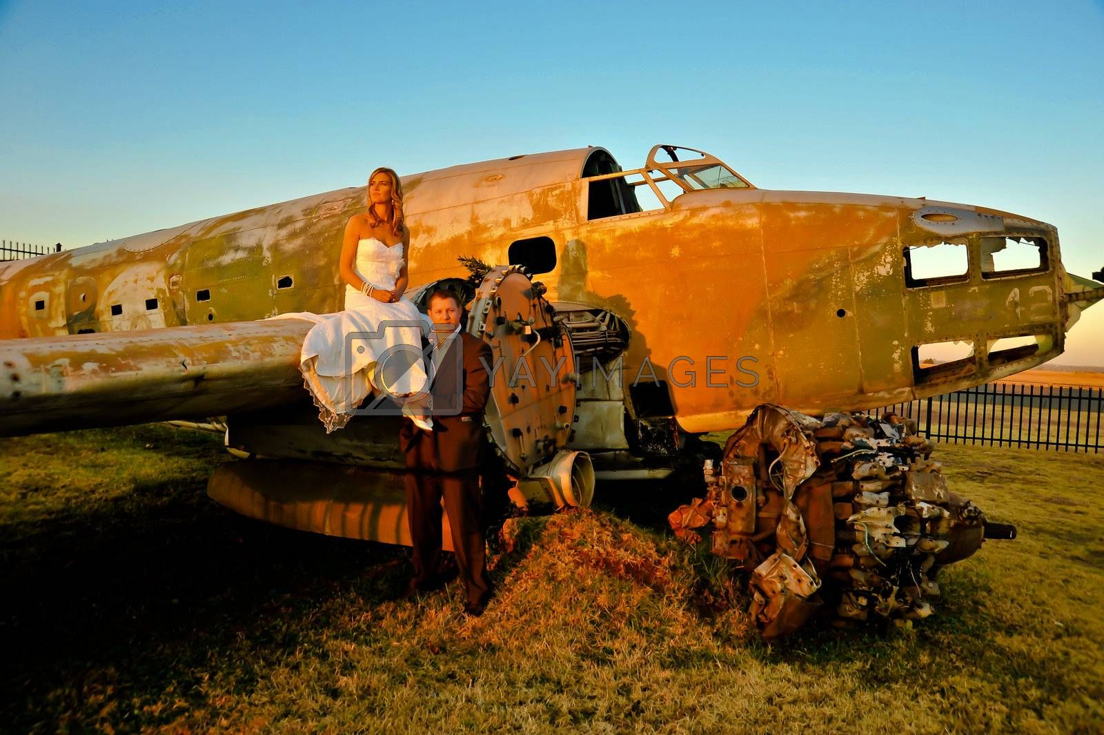 sexy young adult wedding couple standing at crashed DC3 Dakota war plane