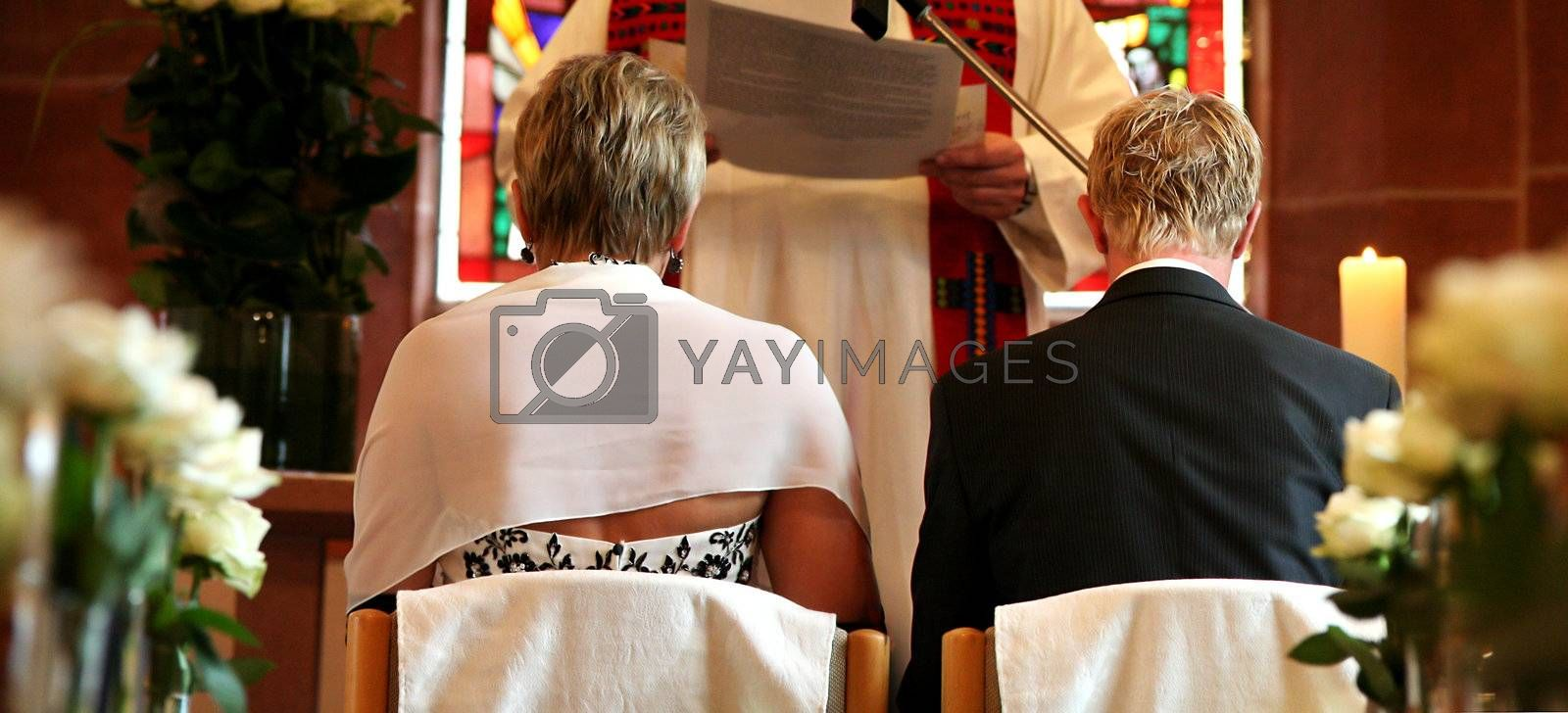 Bride and groom on chairs in the church