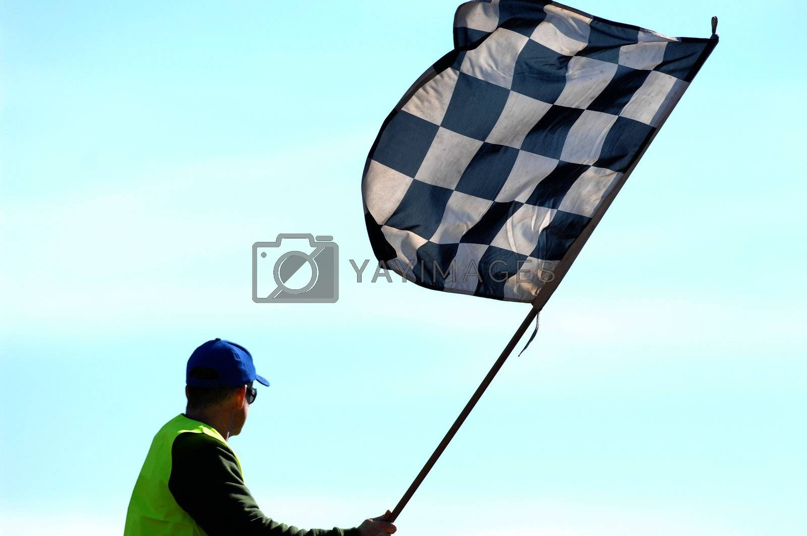 A checkered flag being waved at the completion of a race.