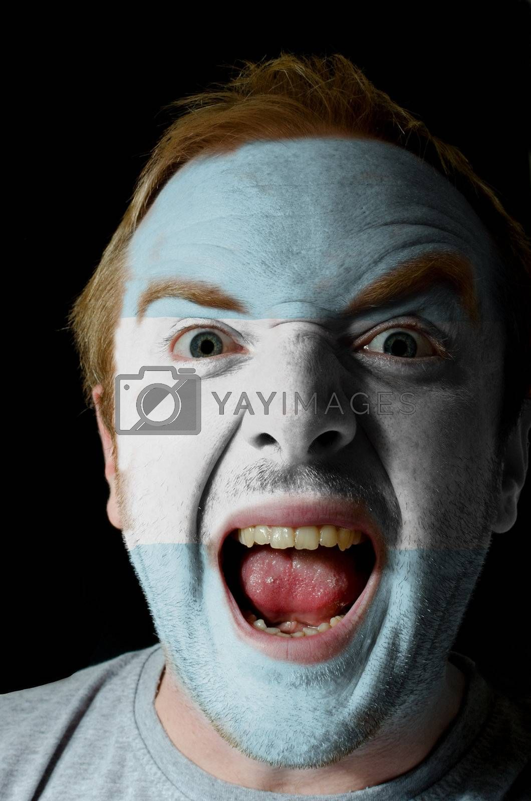 Low key portrait of an angry man whose face is painted in colors of argentinian flag