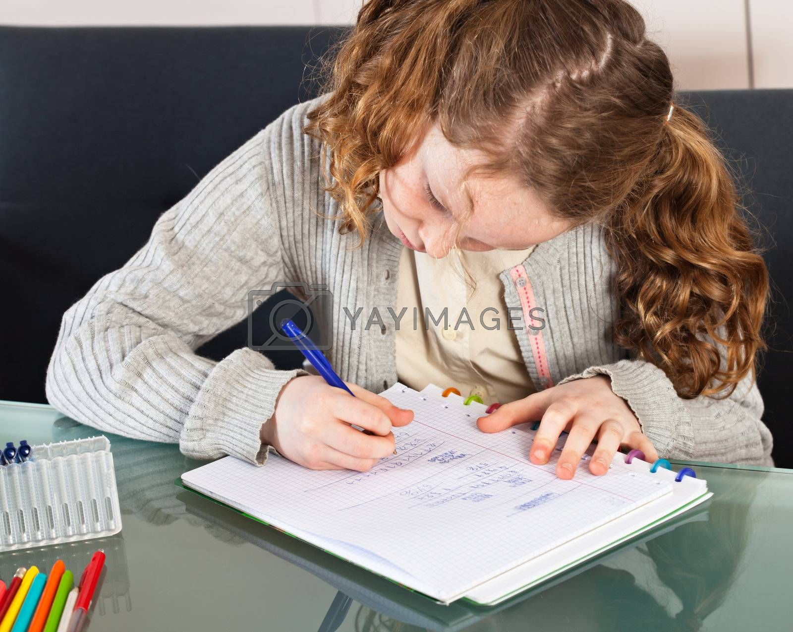 Teenager girl sitting at the table at home and doing her homework