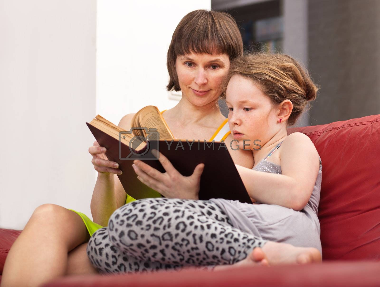 Teenager girl and her mother sitting on sofa and reading book together