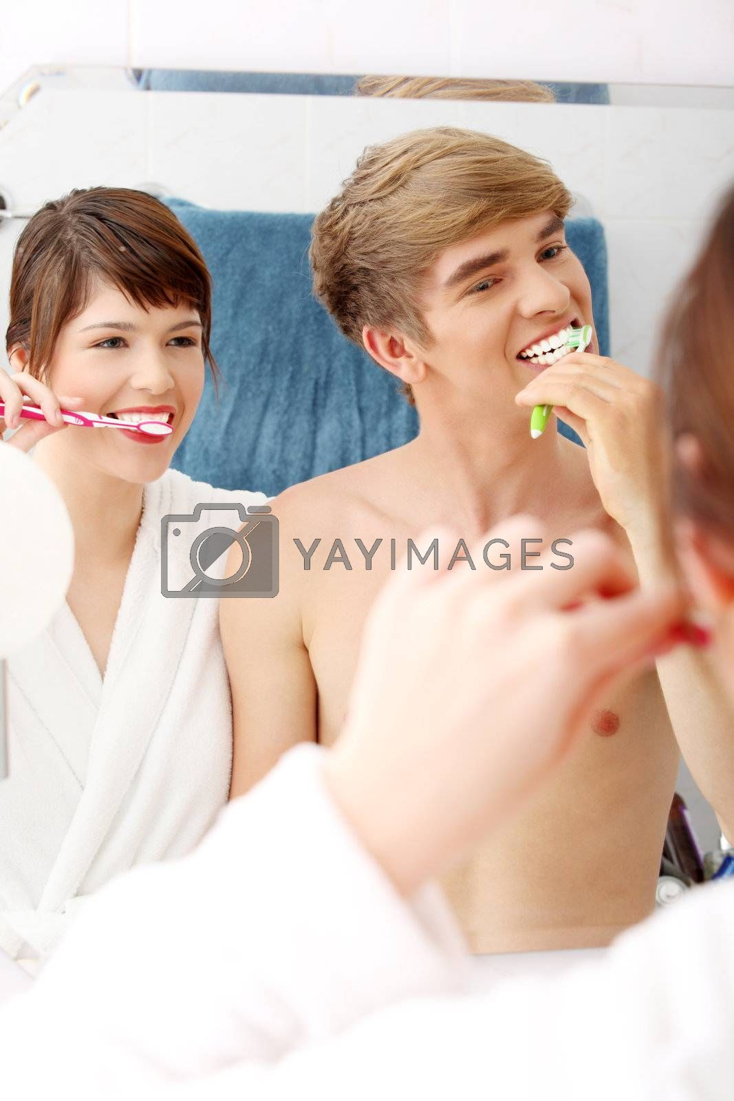 Young couple cleaning teeth together at bathroom.