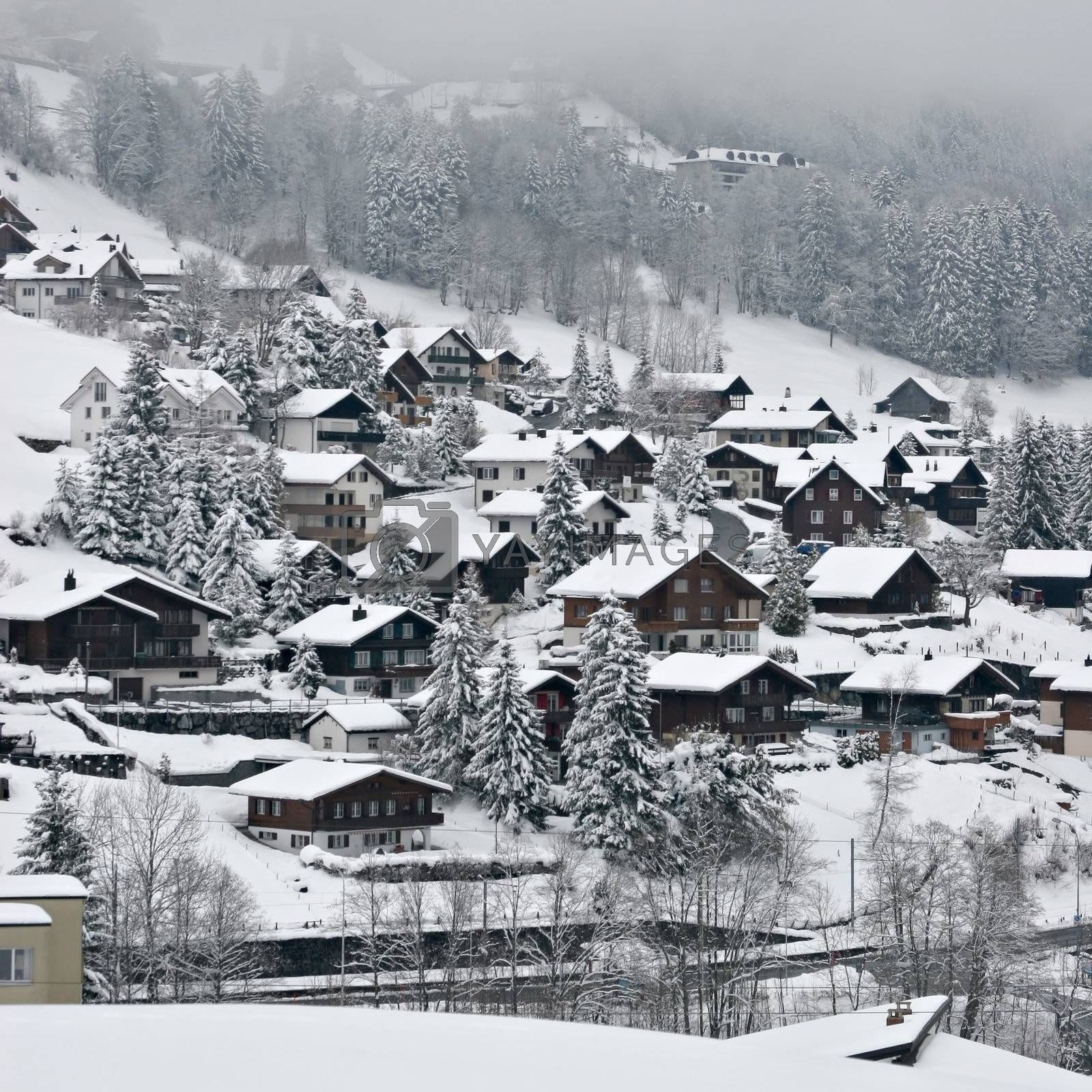 View over a Swiss Village in the Alps, covered in snow during winter.