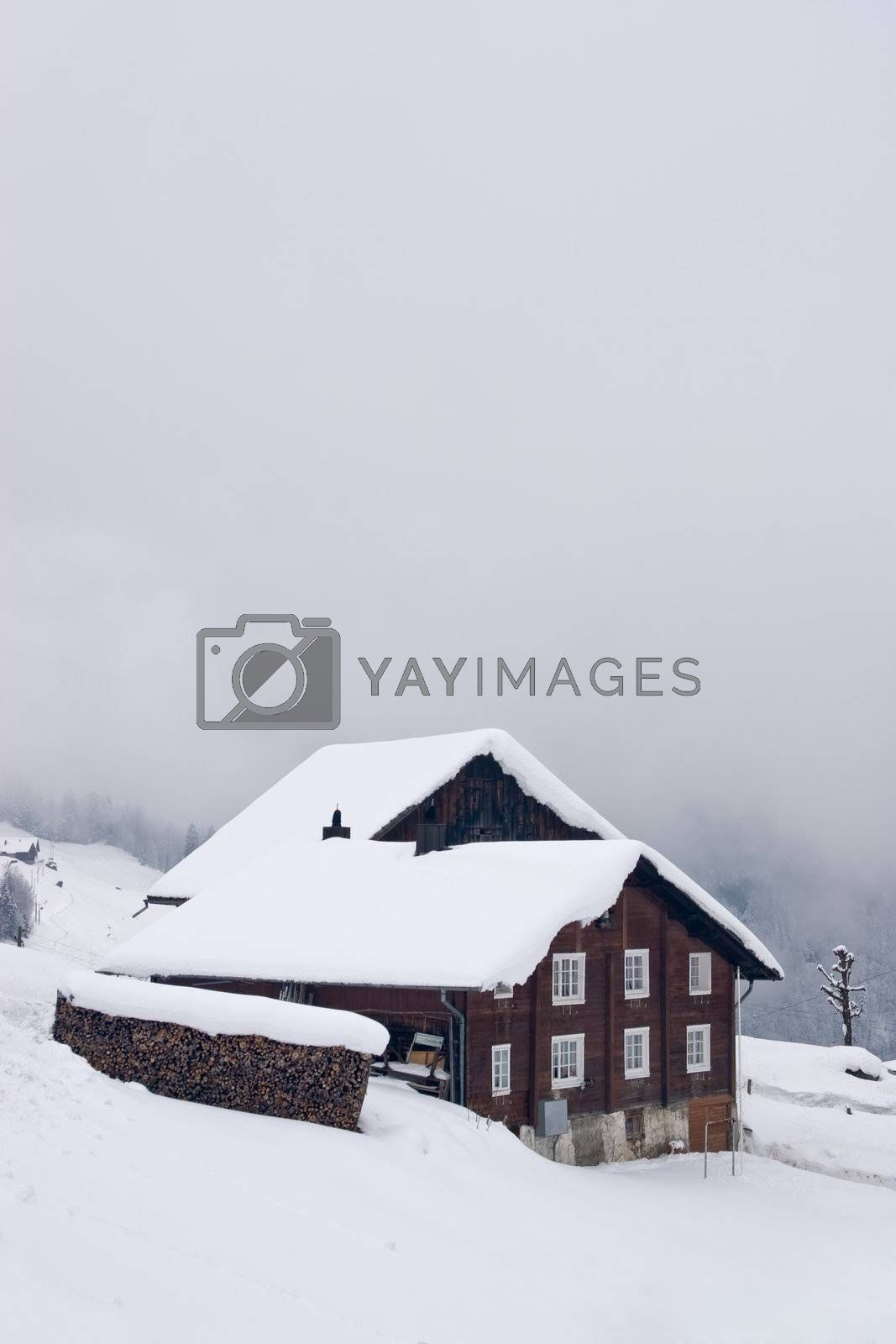 A typical Swiss house covered with snow, in the Alps.