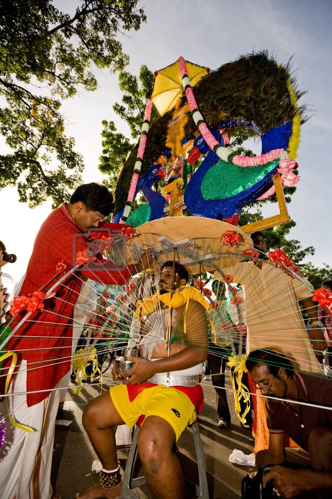 man preparing to carry a heavy kavadi decorated to please the deity