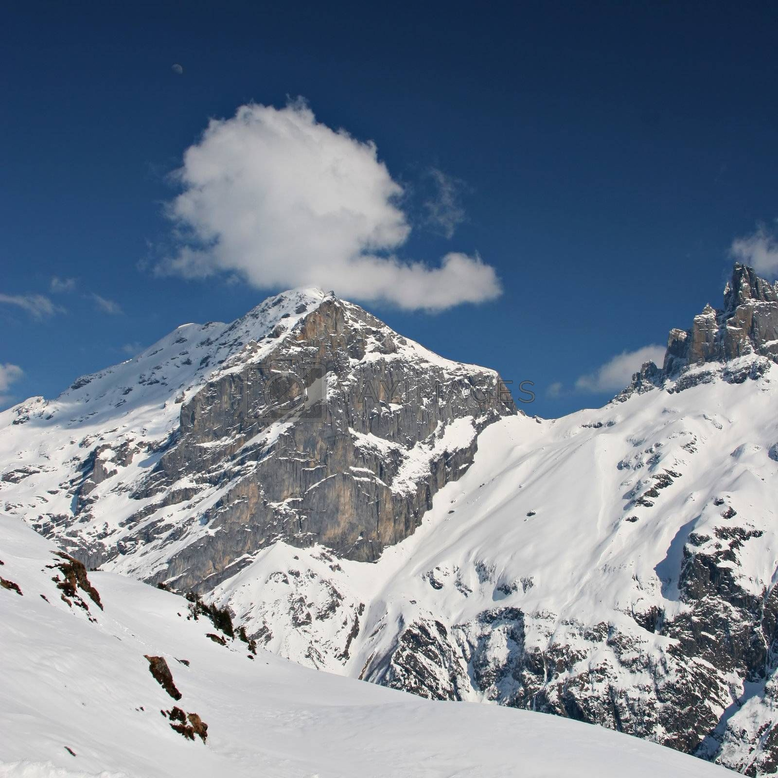Photo of a mountain and a fluffy white cloud on deep blue sky in the Swiss Alps.