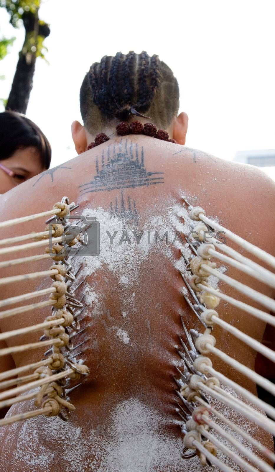 a devotee of thaipusam with hooks pierce through their backs in their beliefs
