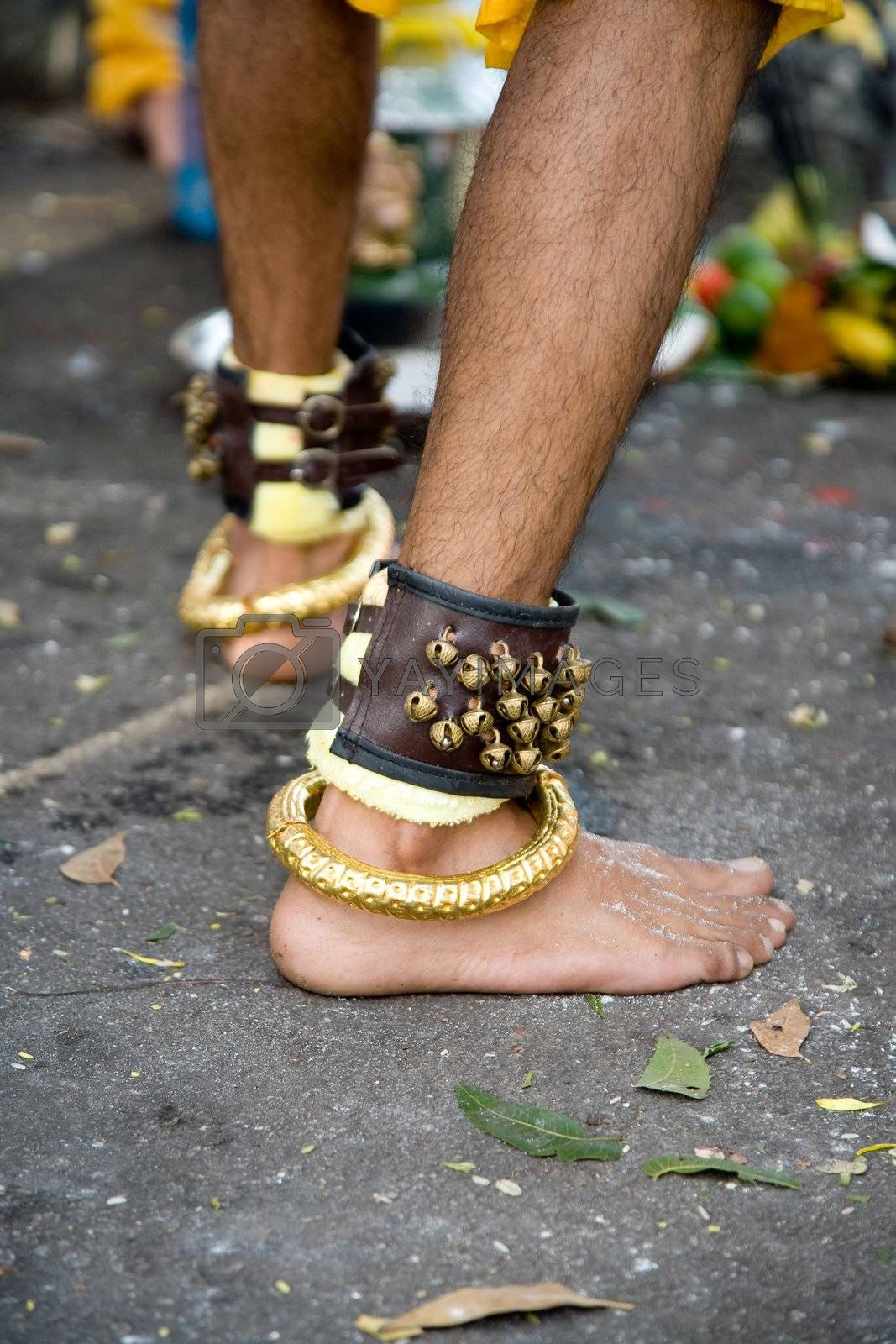 thaipusam devotee wearing a bracelet of bells and gold