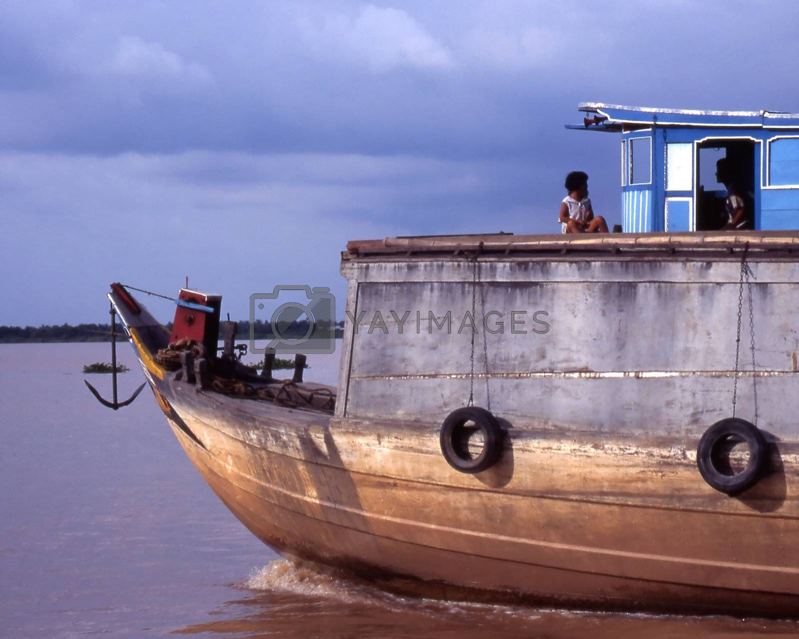 Child sits on roof of wooden house boat. Moving on the Mekong river while in flood.