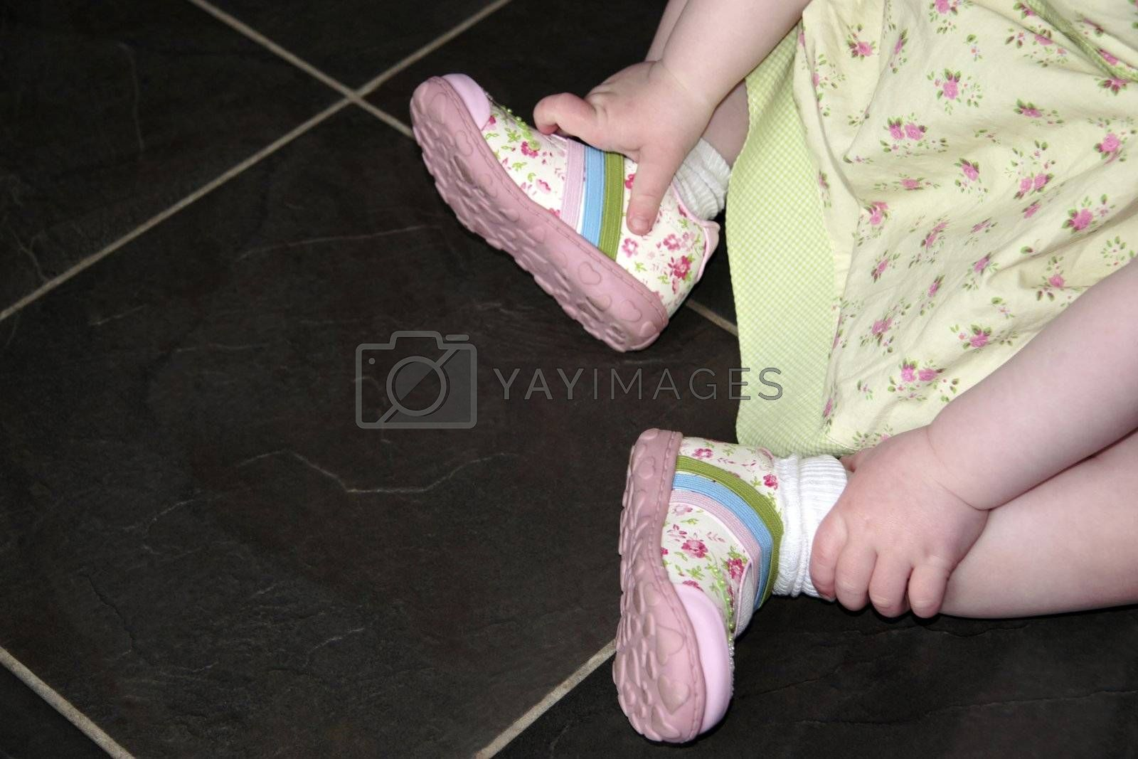 a little baby girl looking at her first new shoes