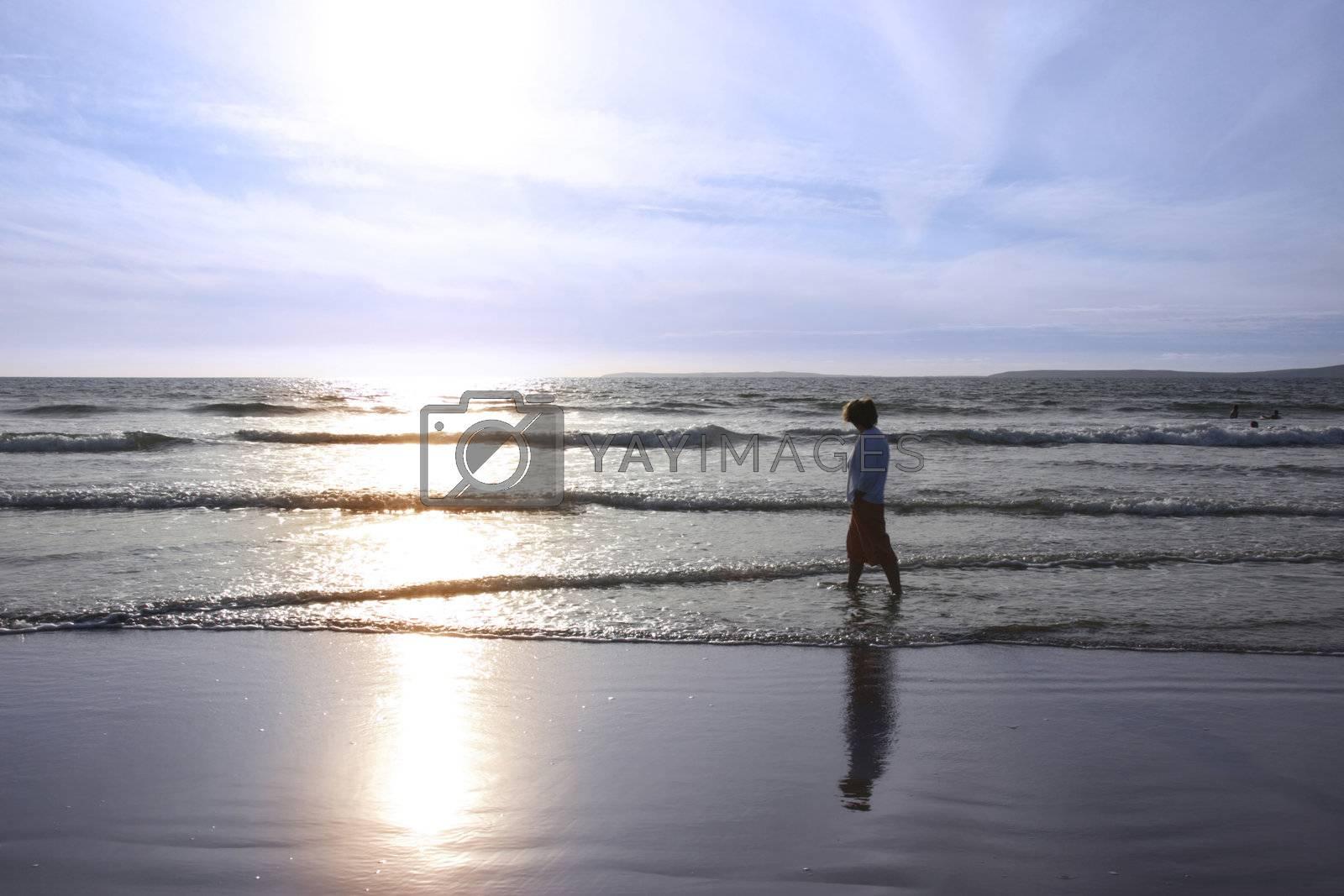 a lady walking in the warm sea