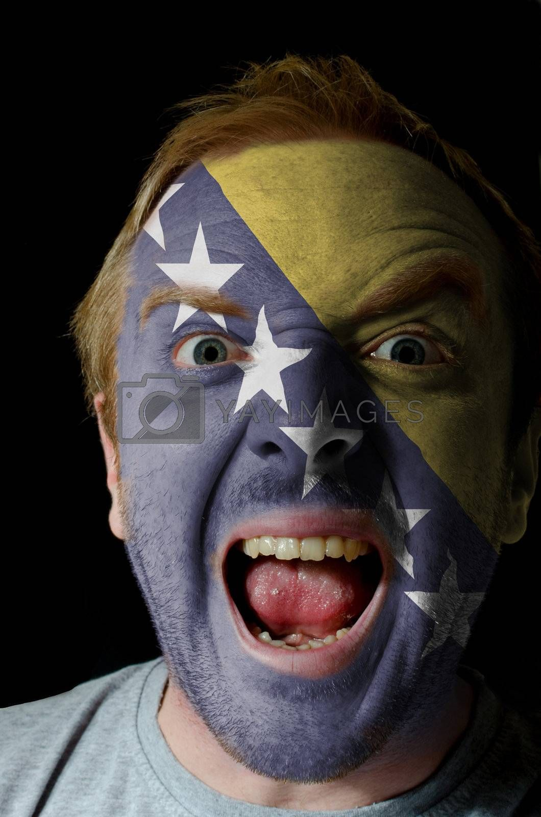 Low key portrait of an angry man whose face is painted in colors of bosnian and hezegovinian flag