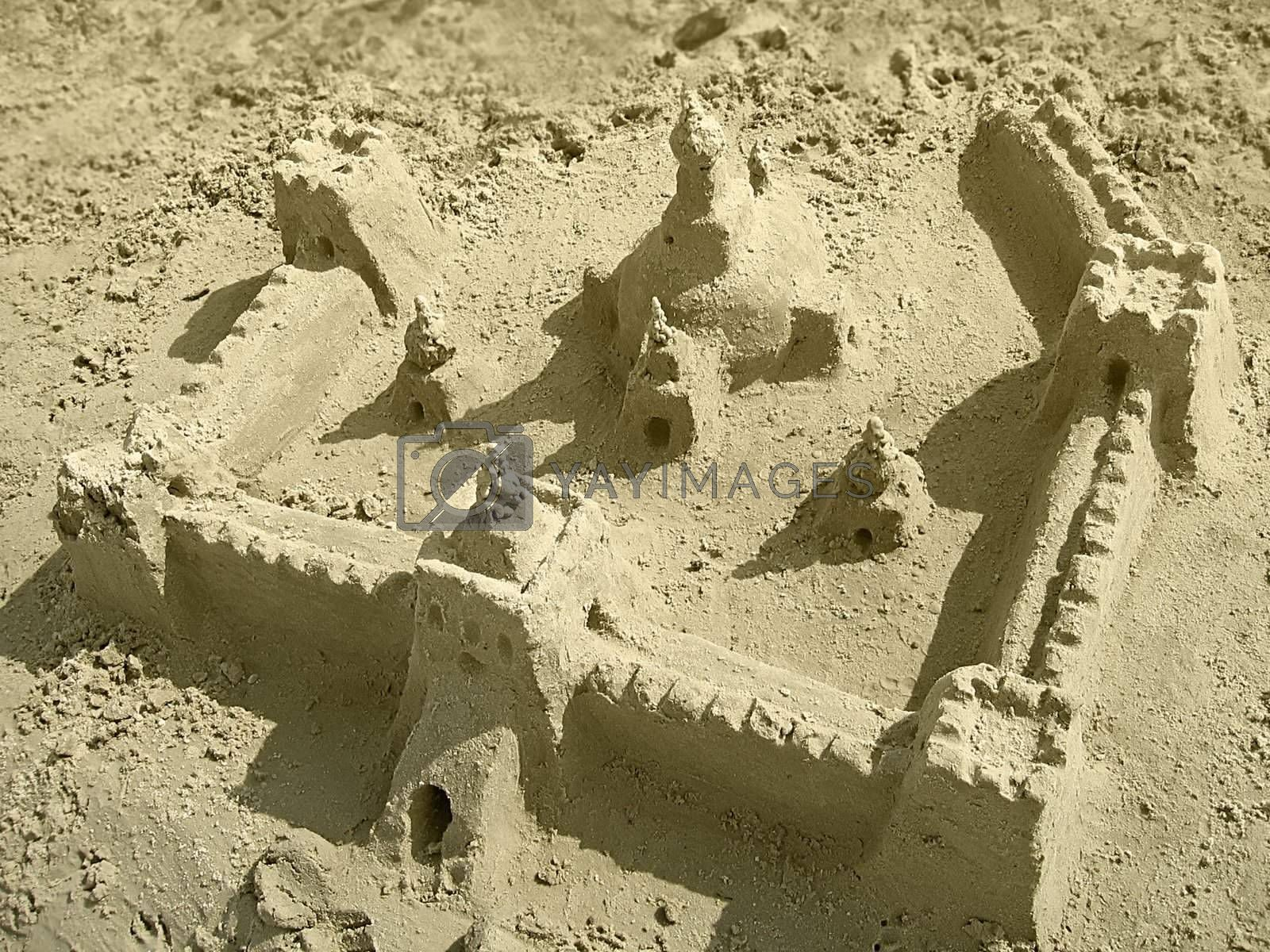a big sandcastle with towers on the beach