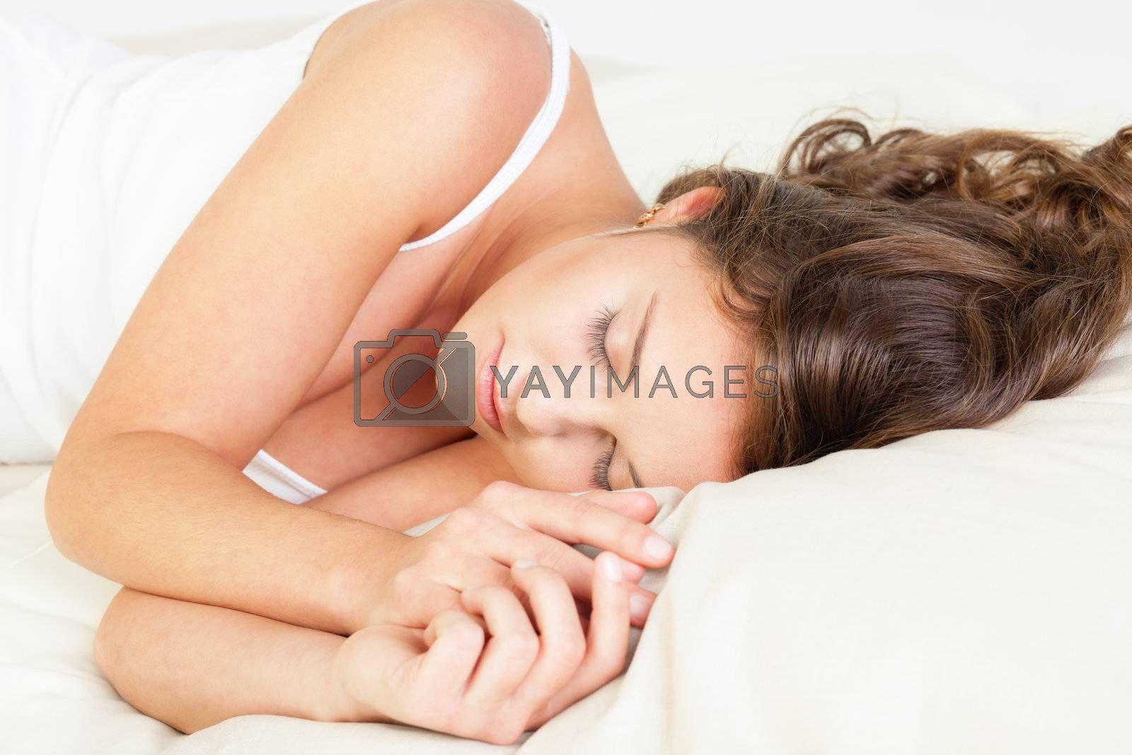 Pretty young woman sleeps in her bed